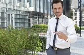 stock photo of middle finger  - Portrait of angry businessman showing middle finger outside office building - JPG