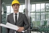 Portrait of confident young male architect holding rolled up blueprints in industry