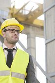Young male engineer wearing hard hat looking away at construction site