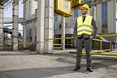 Full length of young male engineer with hands in pockets standing outside industry
