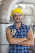 Portrait of confident industrial worker standing arms crossed