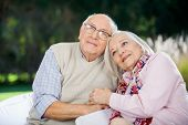 Loving senior couple sitting on chairs and looking away at nursing home
