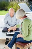 Senior man playing rummy with woman at nursing home porch