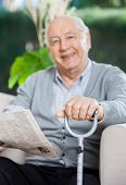 Portrait of happy senior man with newspaper and metal cane sitting on couch at nursing home porch
