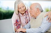 Senior couple looking at each other while using laptop at nursing home