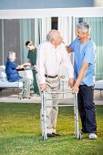 Male caretaker comforting senior man while assisting him in using Zimmer frame at nursing home lawn