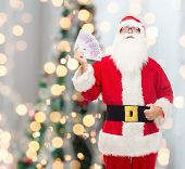 christmas, holidays, winning, currency and people concept - man in costume of santa claus with euro money over tree lights background
