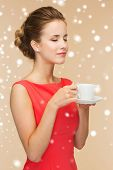holidays, people and drink concept - smiling woman in red dress with cup of coffee over beige background and snow