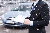 transportation, people, sale and ownership concept - close up of man with clipboard and car documents