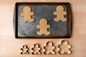 High angle shot of a cookie sheet with three gingerbread man cookies. Below the pan is a row of four cookie cutters of different sizes, Horizontal format on a butcher block kitchen table.
