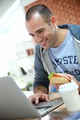 Student eating sandwich in front of laptop