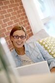 Woman in modern apartment using laptop