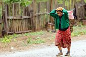 BAAN LOOK KAO LAM, THAILAND, NOVEMBER 19, 2012 : Unidentified woman is carrying food in her grape basket under the rain in the village of Ban look Kao Lam, north Thailand.
