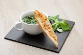 pic of sauteed  - Appetizer sauteed garlic spinach dish in cup baked bread slice with melted cheese served on black stone - JPG