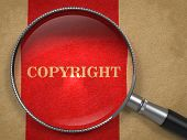 picture of plagiarism  - Copyright through Magnifying Glass on Old Paper with Red Vertical Line - JPG
