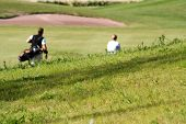 Couple playing golf, focus on grass in front