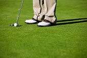 Close-up of man putting golf ball in to hole