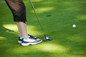Close-up of junior golfer putting golf ball in to hole