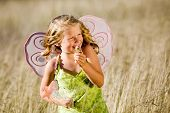 Little girl with butterfly wings and magic wand