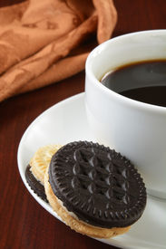 stock photo of duplex  - Duplex cream filled sandwich cookies with a cup of coffee - JPG