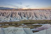 image of butts  - Scenic sunset view of the geological formations of the South Dakota badlands with heavily eroded buttes gullies and spires rising from the surrounding prairie grassland - JPG