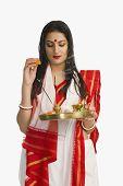 image of pooja  - Woman in a Bengali sari holding pooja thali - JPG