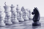 stock photo of time-piece  - Black knight facing white chess pieces on a chess board - JPG