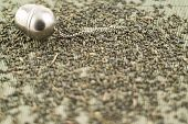 foto of black tea  - Metal tea infuser on scattered black tea over bamboo mat - JPG