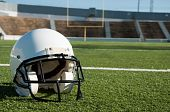 picture of ncaa  - American football helmet on field with goal post in background - JPG