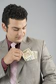 stock photo of indian currency  - Businessman with Indian five hundred rupee banknotes in his pocket - JPG