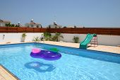 picture of inflatable slide  - Empty swimming pool with inflatable ring and shute on summers day - JPG