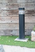 image of lamp post  - Lamp post against a textured wood wall - JPG