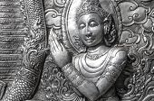 pic of metal sculpture  - A horizontal photographic image of an ancient metal wall sculpture from Wat Srisuphan Temple in Chiang Mai Thailand depicting a crowned man - JPG