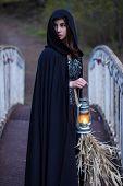 image of cloak  - girl in a black cloak with a lantern on the bridge - JPG