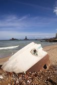 image of kanyakumari  - Rubbles of a building on the beach with Thiruvalluvar Statue in the background - JPG