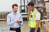 stock photo of warehouse  - Warehouse worker talking with his manager in a large warehouse - JPG