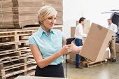 pic of warehouse  - Smiling warehouse manager scanning package in warehouse - JPG