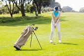 stock photo of take off clothes  - Female concentrating golfer teeing off on a sunny day at the golf course - JPG