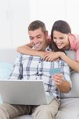 picture of debit card  - Happy couple shopping online through laptop using debit card at home - JPG