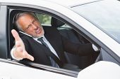 stock photo of outrageous  - Businessman experiencing road rage in his car - JPG