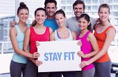 stock photo of fitness  - The word stay fit against fit smiling people holding blank board - JPG