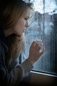 stock photo of raindrops  - melancholic young woman looking through window with raindrops with added filter grain and vignette - JPG