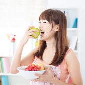 foto of apron  - Happy Asian housewife with apron eating green apple - JPG