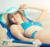 foto of sunbathing woman  - Young lady sunbathing on a beach - JPG