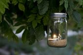 picture of mason  - mason jar with candle that is lit hanging on a tree for decoration for a wedding or outside parties - JPG