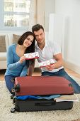 picture of boarding pass  - Portrait Of Happy Young Couple Packing Luggage Showing Boarding Pass - JPG