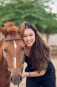 pic of chestnut horse  - Portrait of smiling girl with a chestnut pony looking at the camera - JPG