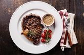 stock photo of ribeye steak  - Medium rare grilled Beef steak Ribeye with grilled cherry tomatoes and Pepper sauce on white plate on wooden background - JPG