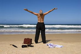 picture of retirement  - Businessman standing on a beautiful beach with arms outstretched - JPG