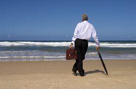 stock photo of retirement  - Retired business man standing on a beautiful beach - JPG